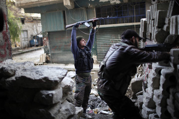 Free Syria Army fighters fire as they fight with Syrian forces loyal to President Bashar al Assad at the front line in Aleppo