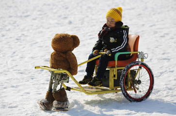 A boy rides on a snow wagon towed by a robot dressed as a Teddy bear during the Ice and snow carnival at Taoranting park in Beijing