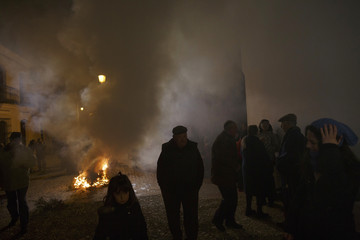 """People gather next to a bonfire during the """"Luminarias"""" annual religious celebration on the eve of Saint Anthony's Day in Alosno"""