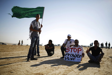 A protester holds a placard as another holds an Islamic movement flag during a demonstration near Rahat