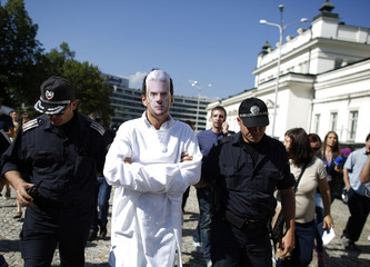 A protester wearing a mask is detained by the police, after breaching the security perimeter in front of the parliament building and  performing a skit mocking Siderov, during a demonstration in Sofia