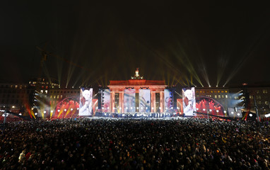 Choir performs on stage in front of Brandenburg Gate next to Border of Light installation in Berlin