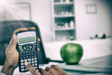 Composite image of hands of businessman using calculator