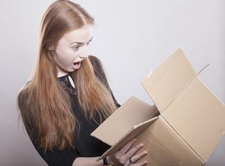 Frau erschrickt beim Blick in einen Karton