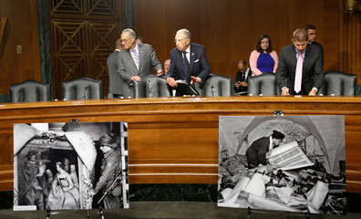Senators Schumer and Grassley are seen behind World War Two photographs before a joint Senate Judiciary Subcommittee on stolen artwork by the Nazis in Washington