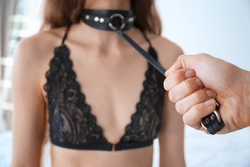 Man holding young prostitute on leash in bedroom