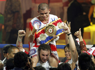 Indonesia's John celebrates atop his trainer Christian's shoulders after winning his WBA featherweight title fight against his compatriot Yordan in Jakarta