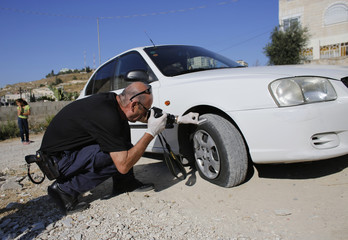 An Israeli police crime scene investigator takes a picture of a slashed tire on a car in East Jerusalem
