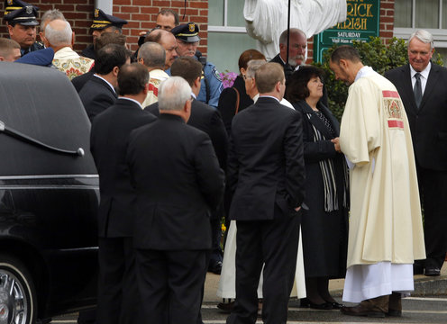 A priest greets family and friends of MIT police officer Sean Collier after his funeral in Stoneham