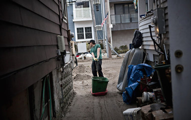Phil Amabile, a volunteer, drags a bucket of sand out from a backyard, while cleaning up damage caused by Hurricane Sandy, in the Rockaway Beach neighborhood of Queens, New York
