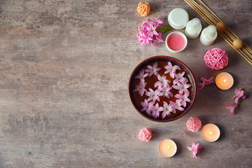 Beautiful spa composition of flower petals with water in bowl and candles on textured background