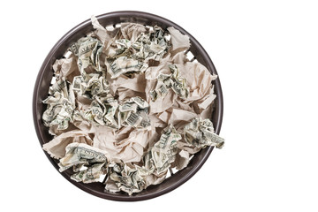 Garbage basket full of toilet paper and crumpled dollars, top view, isolated on white background
