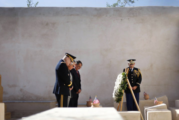 U.S. Secretary of Defense Panetta, U.S. Ambassador to Libya Cretz, and Gen. Carter Ham, Commander of U.S. Africa Command bow their heads during the wreath laying ceremony at the grave site of 13 U.S. Navy sailors at the Protestant Cemetery in Tripoli