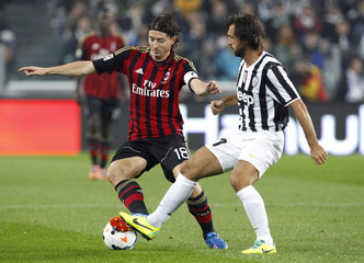 Juventus' Pirlo is challenged by AC Milan's Montolivo during their Italian Serie A match in Turin