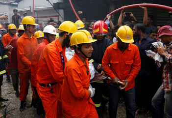 Rescue team members remove a dead body at a food and cigarette packaging factory after a fire broke out outside of Dhaka