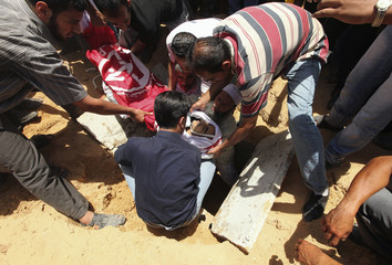 Palestinians lower the body of militant Bassam Badwan into the grave during his funeral in Gaza City