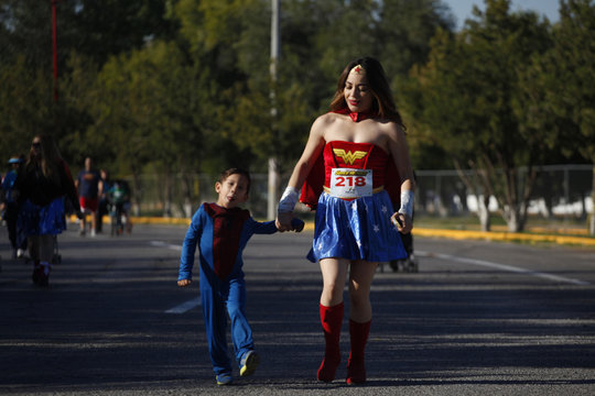 """A mother walks with her son during the """"Superheroes Corriendo Por Peque?os Inocentes"""" race at Chamizal park in Ciudad Juarez"""