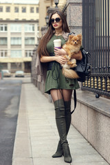 Street style portrait. Stylish girl with long straight brown hear wearing hessian boots or jackboots, grid pantyhose and sweatshirt. Woman with german spitz.