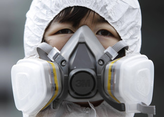 An anti-nuclear protester wears a radiation protection suit during a rally opposing the Nuclear Security Summit in Seoul