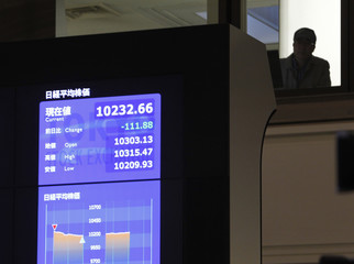 A visitor is seen next to a large screen showing the Nikkei average before a ceremony marking the end of trading for 2010 at the headquarters of Tokyo Stock Exchange in Tokyo