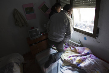 Ronale de la Cruz and his wife Nalda look out the window of their apartment as they wait to be evicted after failing to pay their mortgage, in Madrid