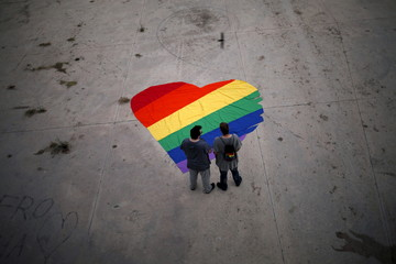 Franco and his partner Varon stand next to a heart-shaped cloth with rainbow colors as they pose for a photo, to mark Gay Pride day, in downtown Malaga