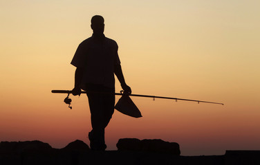 A man carries a fishing rod during sunset along the shoreline in the Mediterranean city of Alexandria