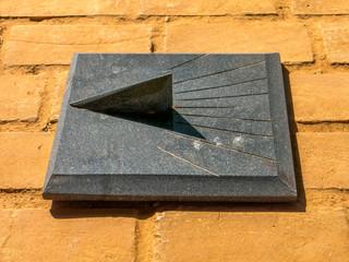 Granite Sundial - sun clock on orange brick floor