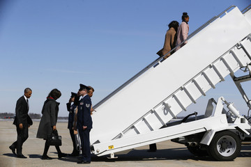 Obama and his family are saluted as they board Air Force One for travel to Alabama from Joint Base Andrews, Maryland