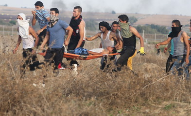 A wounded Palestinian protester is evacuated after he was shot by Israeli troops near the border between Israel and Central Gaza Strip