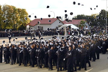 Police students throw their hats during a graduation ceremony at the National Police Academy in Nimes