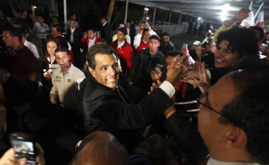 Pena Nieto, presidential candidate of PRI greets supporters after exit polls showed him in first place, in Mexico City