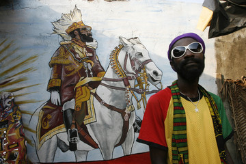 A member of the Rastafari movement stands beside a drawing of the late Ethiopian Emperor Haile Selassie as he awaits for the arrival of Ivorian officials in the Rasta village of Port Bouet