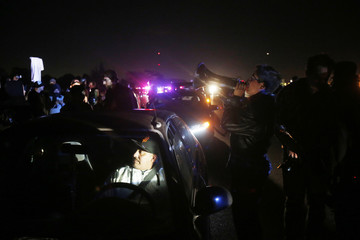 A stranded motorist sits in his car as protesters block traffic on Highway 80 during a march in Berkeley