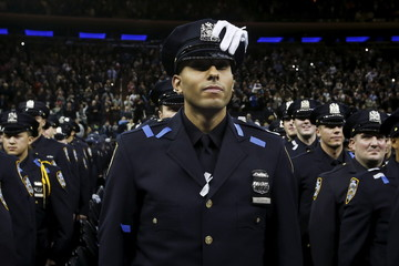 A newly inducted New York Police officer stands with a white glove on his cap as he takes part in a graduation ceremony at Madison Square Garden in the Manhattan borough of New York