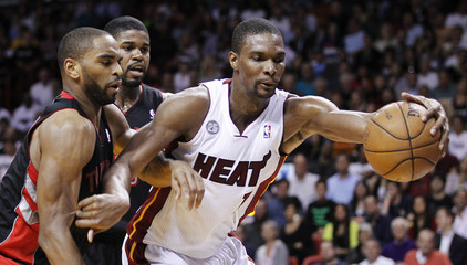 Toronto Raptors' Anderson and Johnson defend Miami Heat's Bosh during their NBA basketball game in Miami