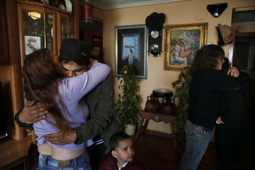 Asun Querol Revilla embraces her son-in-law David Mendoza while her husband Emilio Martin Manjon hugs their daughter Sandra upon learning that their eviction by the Municipal Housing and Land Company was suspended in Madrid