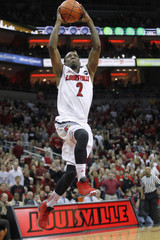 University of Louisville's Russ Smith dunks the basketball over top of Syracuse University defense during the second half of play in their NCAA basketball game at Yum! Center in Louisville