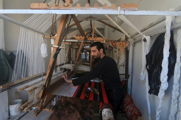 A man works on a loom to make traditional carpets in the town of Ariha