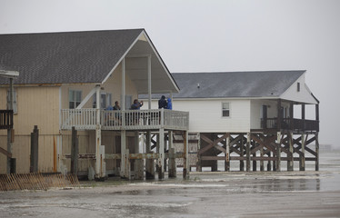 Tourists take photos of the surf from their beach houses during Hurricane Arthur, on the west end of Ocean Isle Beach, North Carolina