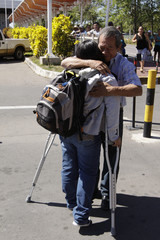 A Salvadoran woman is hugged by her father at El Salvador's international airport in Comalapa