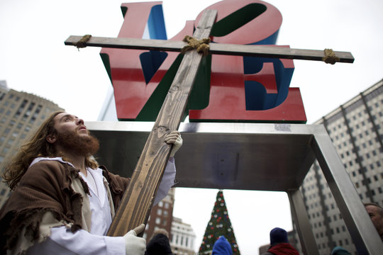 """Upon reaching LOVE Park in Center City, Michael Grant, 28, """"Philly Jesus,"""" lifts the 12 foot cross he had carried 8 miles through North Philadelphia as part of a Christmas walk to spread the true message of the holiday"""