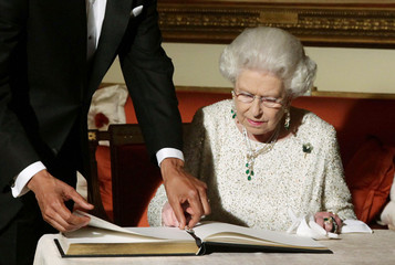 U.S. President Barack Obama flips to the page where Britain's Queen Elizabeth signs the guest book at Winfield House in London