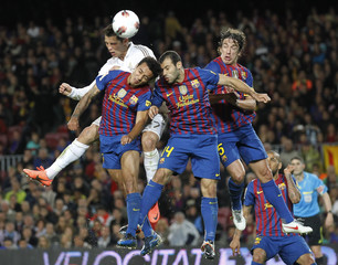 """Real Madrid's Ronaldo heads the ball with Barcelona's Thiago, Mascherano and Puyol during their Spanish first division """"El Clasico"""" soccer match in Barcelona"""