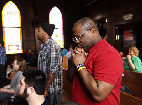 Holmes prays during a Sunday service at the Open Door Community Fellowship Church in Louisville, Kentucky