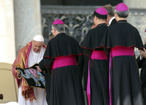 Pope Francis receives a gift from a bishop during the general audience in St. Peter's Square at the Vatican
