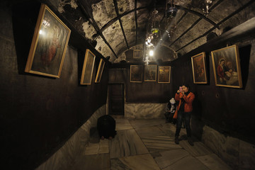A visitor takes pictures inside Grotto in Church of Nativity in Bethlehem ahead of Christmas