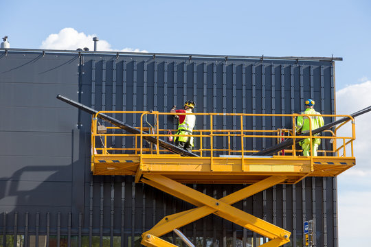 Workers on the aerial work platform at facade installation work