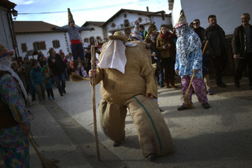 A person dressed as Ziripot, a traditional figure stuffed with straw, walks in front of the figure of Miel Otxin during carnival celebrations in Lantz