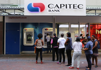 Customers queue to draw money from an ATM outside a branch of South Africa's Capitec Bank in Cape Town